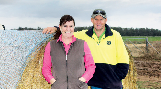 A man and woman standing in front of bale of hay