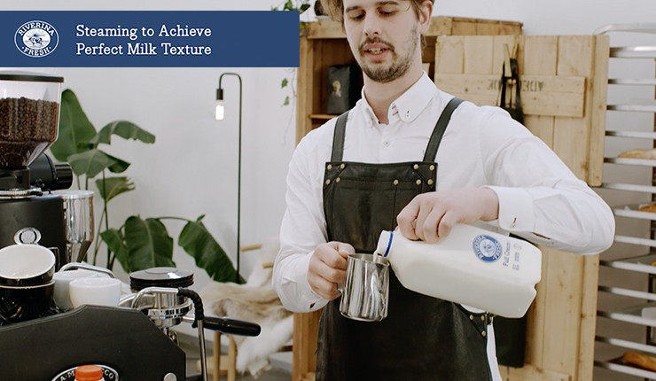 "Barista pouring Riverina Fresh milk with text ""Steaming to Achieve Perfect Milk Texture"""