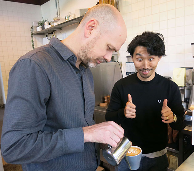 Man making thumbs up sign watching milk being poured into coffee