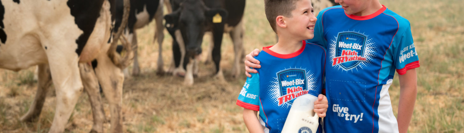 Two children standing in front of cows holding Riverina Fresh milk wearing Weet-Bix shirts