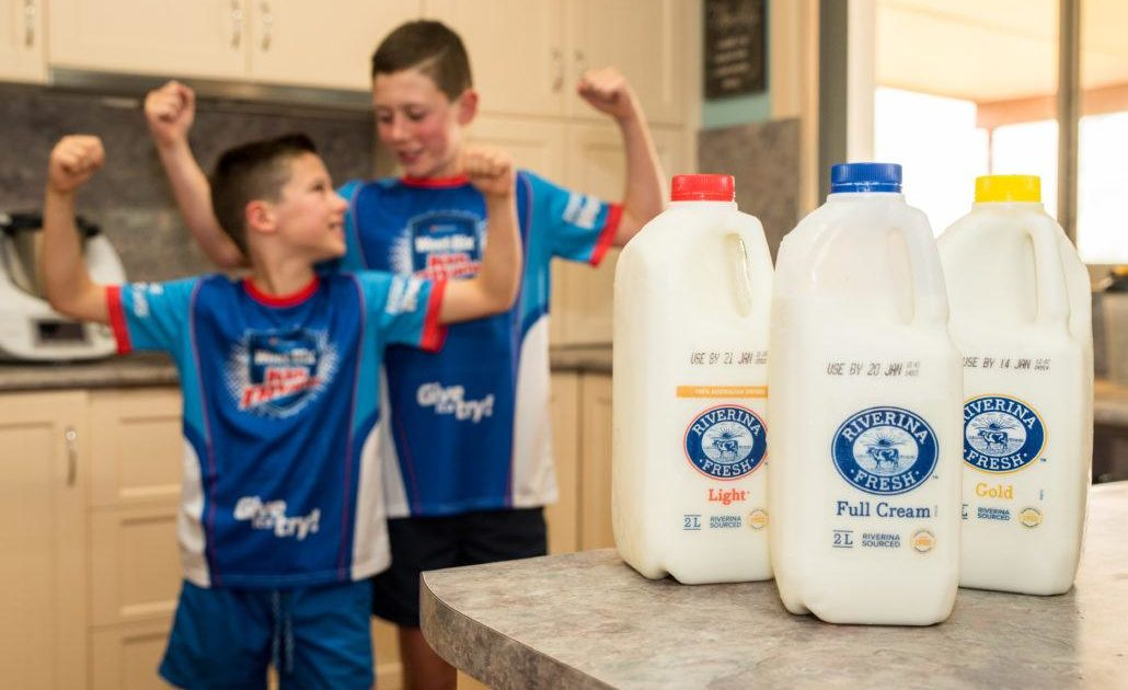 Two boys smiling and flexing arms behind Riverina Fresh milk