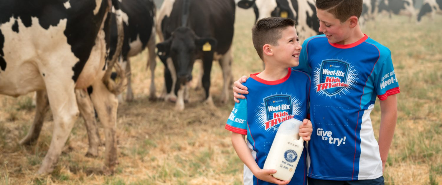 Two children standing in front of cows holding Riverina Fresh milk wearing Weet-Bix TRYathalon shirts